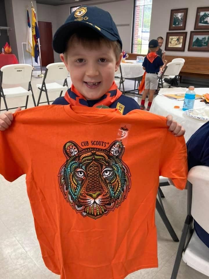 Cub Scout proudly displaying his new t-shirt.